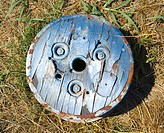 Old round wooden cog lying on ground