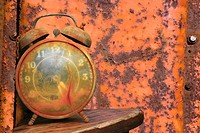Old weathered alarm clock against rusty orange metal background