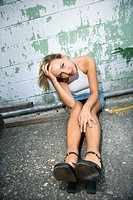 Caucasian mid_adult blonde woman sitting against wall of building with head in hand and looking at viewer