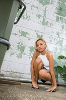 Caucasian mid_adult blonde woman kneeling beside building in alley looking at viewer