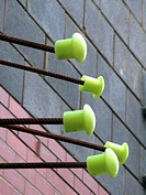 Reinforcing rods with green plastic caps, against brick wall