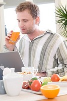 man working on laptop during breakfast