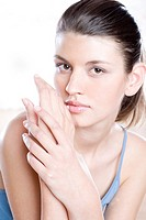 young woman putting cream on hands
