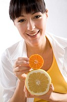 smiling woman with manadarine and grapefruit