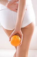back of a woman holding orange