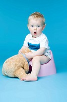 small boy sitting with teddy bear on toilet