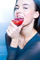 young woman biting pomegranate