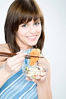 young woman eating chicken nugget with sticks