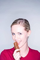 young woman eating chocolate bar