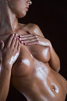 young woman applying oil on breast
