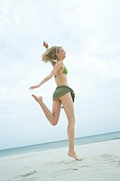 Woman jumping on the beach (thumbnail)