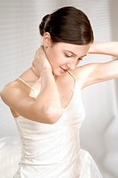 Young woman massaging neck (thumbnail)