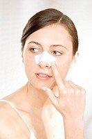 young woman with cleansing strip on nose