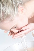 woman washing face with water