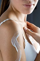 young woman creaming shoulder