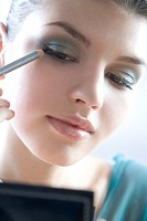 Young woman using eyeliner (thumbnail)
