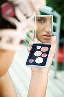 Young woman doing make up (thumbnail)