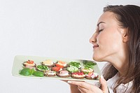 Young woman holding plate with sandwiches