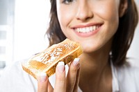 Young woman eating sandwich with honey