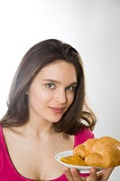 Young woman eating croissant with jam