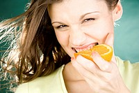 Young woman eating orange