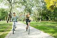 Young women riding bicycles in park