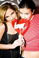 Two girls eating heart shaped lollipop