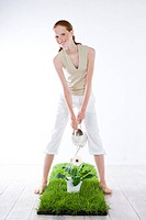Young woman watering plant (thumbnail)