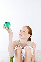 young woman holding green ball