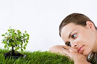 woman looking at bonsai tree