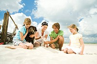 Family on beach playing with dog (thumbnail)