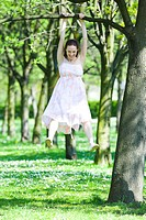 Girl hanging on a branch