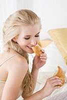 Woman eating croissant in bed