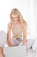 Woman working on laptop in bed (thumbnail)