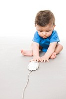 Baby on floor playing with computer mouse