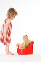 child teaching teddy bear how to use potty