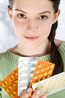 woman holding various blister packs of pills