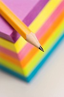 Close up of sharp pencil on stack of colorful sticky notes