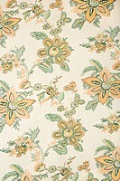 Close_up of vintage fabric with golden flowers and green leaves printed on polyester
