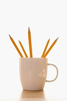 Five pencils in a coffee cup with pointed ends up