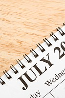 Close up of spiral bound calendar displaying month of July