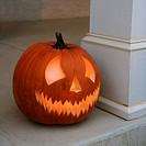 Carved Halloween pumpkin sitting on doorstep (thumbnail)