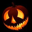 Carved Halloween pumpkin glowing in the dark.