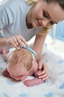 mum brushing babys head