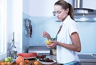 woman eating melon in the kitchen
