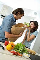 couple unpacking shopping bags in kitchen