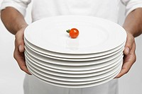 Chef holding stack of dinner plates with single cherry tomato on top mid section