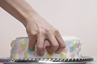 Woman's hands on cake close_up
