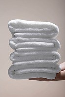 Woman's hands holding stack of folded towels close_up