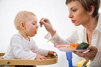 mum feeding baby girl